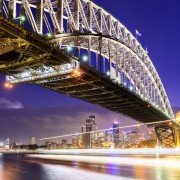 The blurred lights of a ferry boat passing under Sydney Harbour Bridge at twilight, Australia.